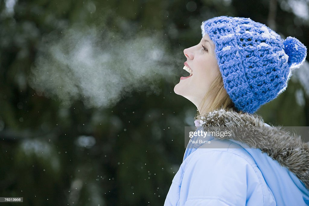 Young woman wearing winter hat, laughing, outdoors
