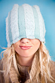 Young Woman Wearing Winter Hat Pulled Down Over Eyes
