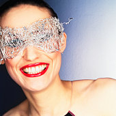Young woman wearing wire mask, smiling, portrait (Digital Enhancement)