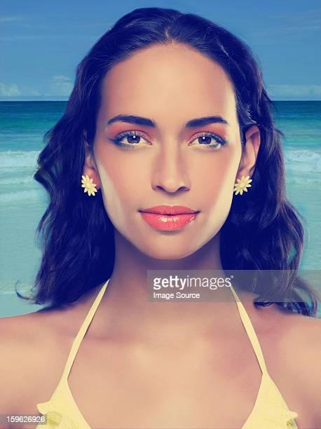 Young woman wearing yellow bikini and earrings