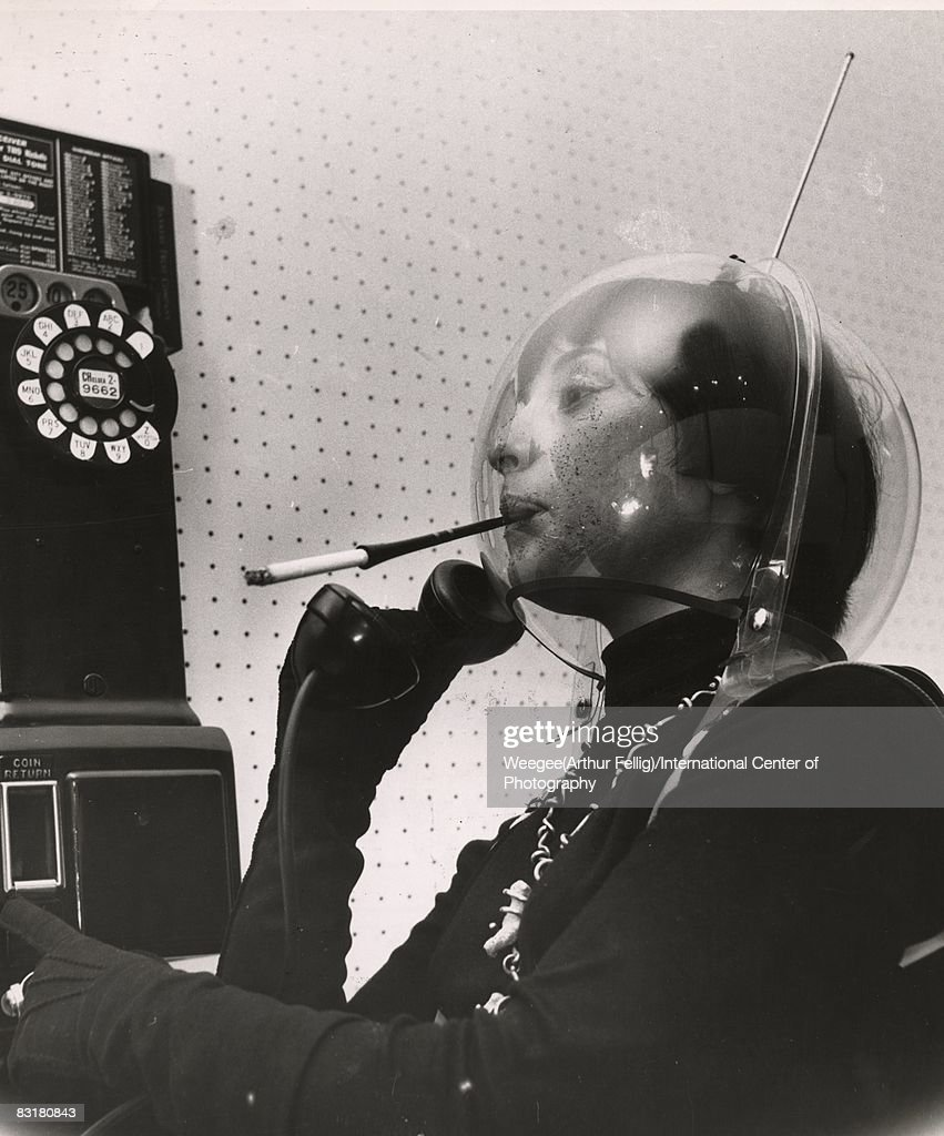 A young woman wears a plastic globe on her head, like an alien or an astronaut, smoking a cigarette in a holder and holding the receiver of a pay telephone, in Greenwich Village, New York, New York, mid 1950s. (Photo by Weegee (Arthur Fellig)/International Center of Photography/Getty Images)