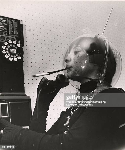 A young woman wears a plastic globe on her head like an alien or an astronaut smoking a cigarette in a holder and holding the receiver of a pay...