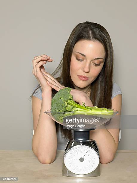 Young woman weighing broccoli