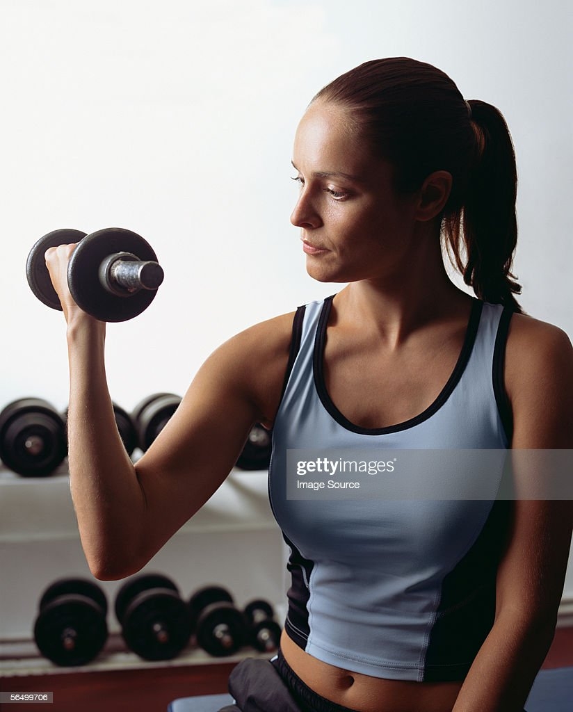 Young woman weightlifting : Stock Photo