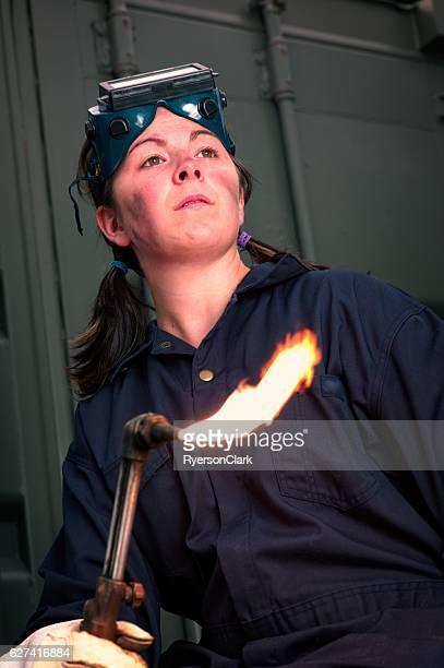 Jeune femme soudeur avec torche de flamme, cadre industriel.