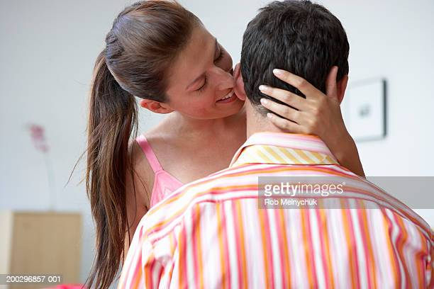 Young woman whispering in man's ear, smiling