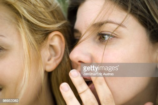 Young woman whispering secret into friend's ear, close-up