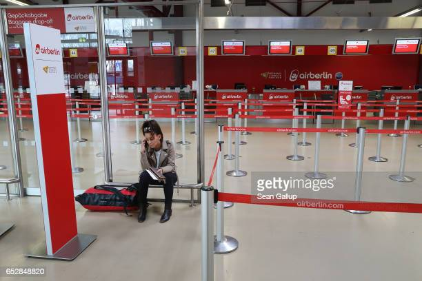 A young woman who said she did not mind being photographed and whose flight to Munich was cancelled sits in the Air Berlin checkin hall during a...