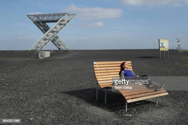 A young woman who said she did not mind being photographed rests on a bench on a hill that is actually a slag heap from a former nearby coal mine on...