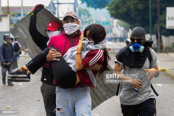 TOPSHOT A young woman who was overcome by tear gas shot by tiot police is carried away by fellow demonstrators when opposition activists clashed with...