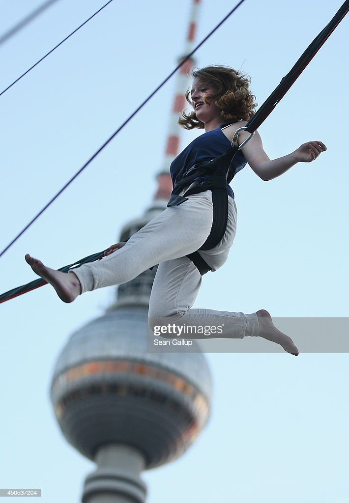 A young woman, who was visiting from Stuttgart and was in Berlin for the first time in her life, jumps on a trampoline in a bungee harness at Alexander Platz as the broadcast tower stands behind on June 12, 2014 in Berlin, Germany. Alexanderplatz is among the coty's most popular landmarks.