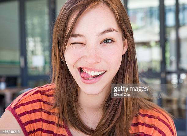 Young woman winking with her tongue out