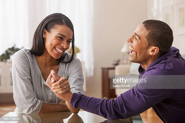 Young woman winning arm wrestling against boyfriend