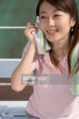 A young woman wiping her perspiration : Stock Photo