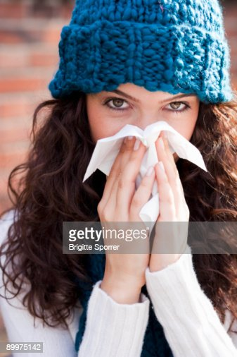 young woman wiping nose : Stock Photo