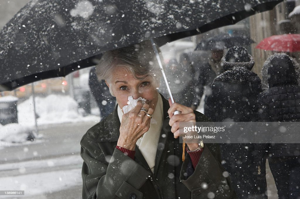 Young woman wiping nose while walking in snow