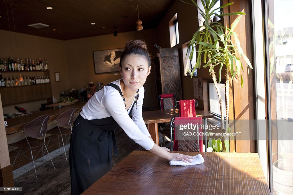 Young Woman Wiping Table : Stock Photo