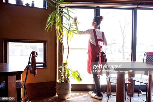 Young Woman Wiping Window