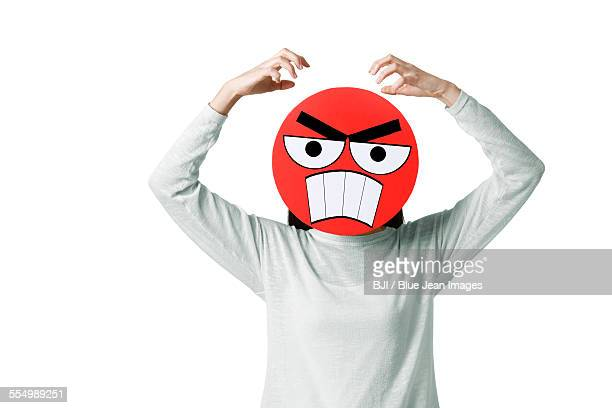Young woman with a angry emoticon face in front of her face