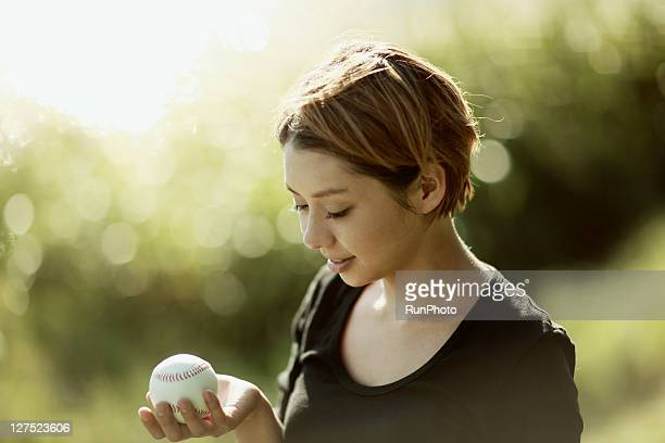 young woman with a baseball near the lake
