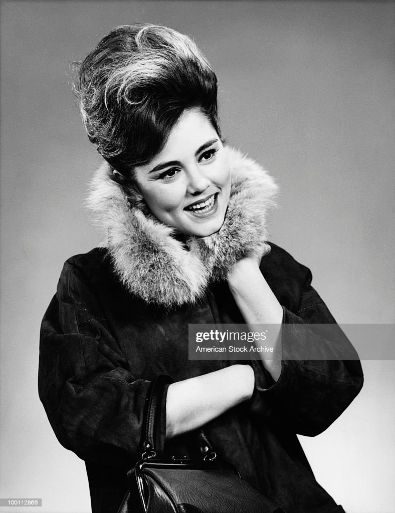 A young woman with a beehive hairstyle and a coat with a fur collar, circa 1967.
