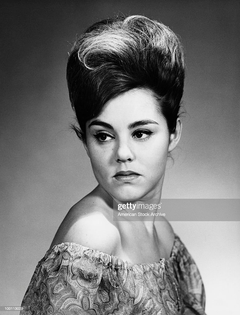 A young woman with a beehive hairstyle and wearing an off-the-shoulder dress, circa 1967.