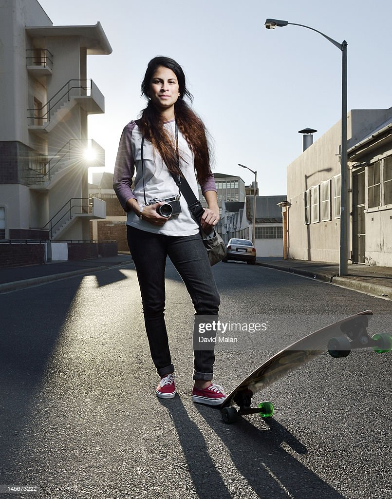 Young woman with a camera and skateboard