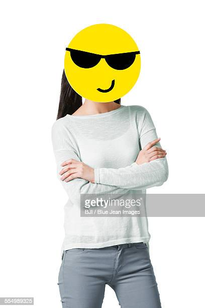 Young woman with a cool emoticon face in front of her face