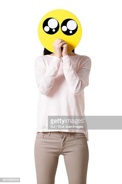 Young woman with a cute emoticon face in front of her face