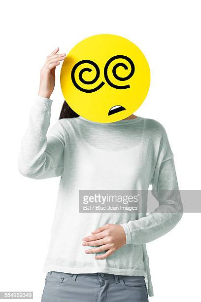 Young woman with a dizzy emoticon face in front of her face
