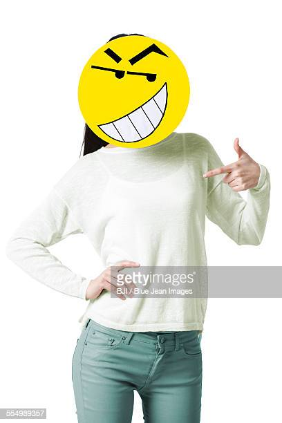 Young woman with a happy emoticon face in front of her face