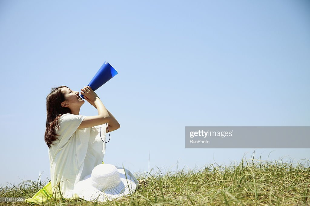 young woman with a megaphone to cheer : Stock Photo