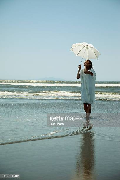 young woman with a parasol into the sea
