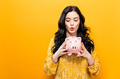 Young woman with a piggy bank on a yellow background