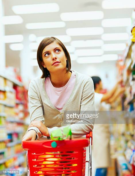 Young woman with a red shopping cart at supermarket