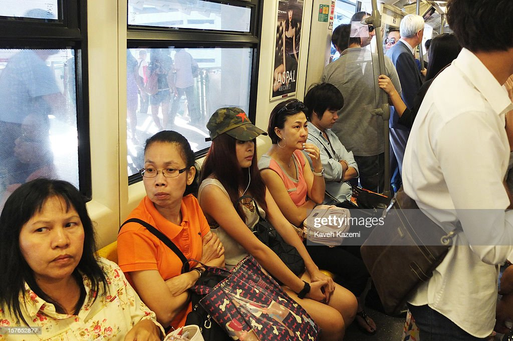 A young woman with a red star sewn on her military style cap sits on the sky train on October 25, 2012 in Bangkok, Thailand.