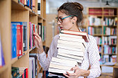 Attractive young woman wearing pink pale shirt with dots and fashionable glasses holding a stack of books in the library surrounded by bookshelves with colorful books. Book grabbing woman.