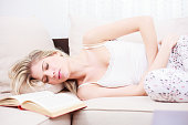 Beautiful young woman with a stomachache lying on sofa with closed eyes. Brightly lit room