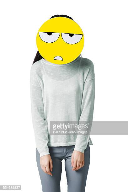 Young woman with a tired emoticon face in front of her face