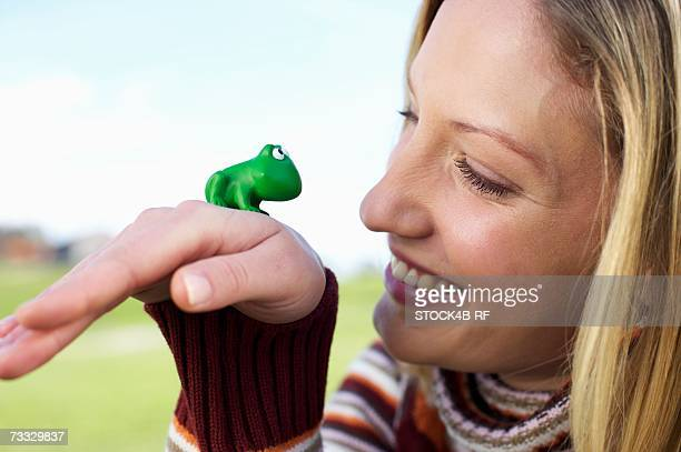 Young woman with a toy frog on the back of her hand, close-up