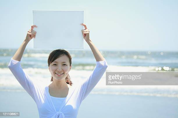 young woman with a white board at the beach,blank