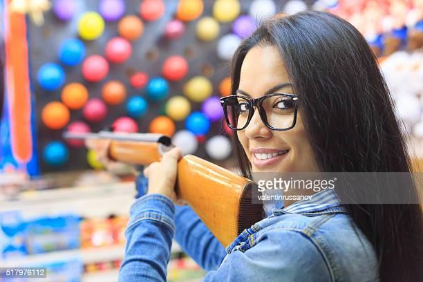 Young woman with air gun for pop a ballon game