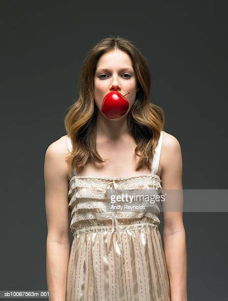 Young woman with apple in mouth, close-up, portrait (digital composite)