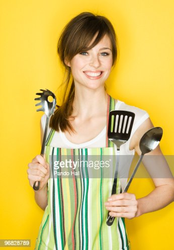 Young woman with apron and cooking utensils : Stock Photo