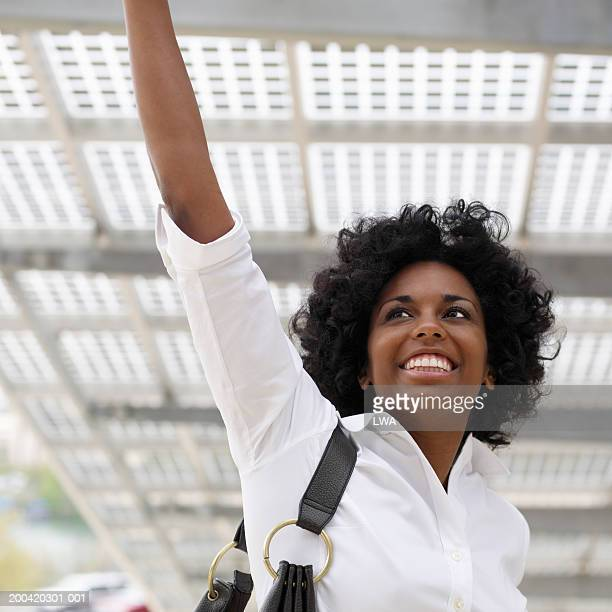 Young woman with arm raised, smiling