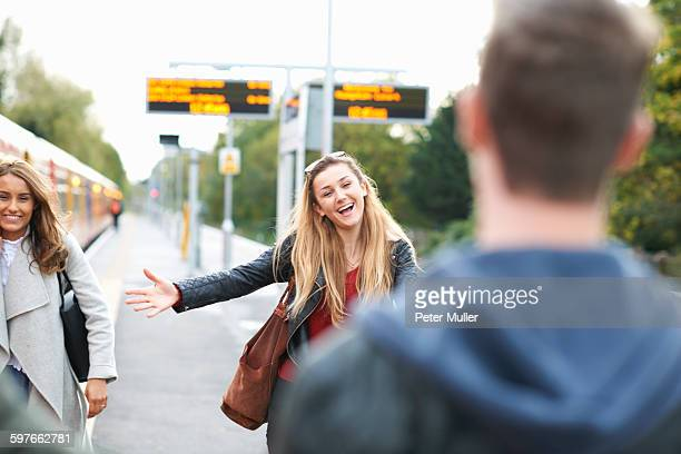 Young woman, with arms open, greeting young man, at railway station