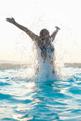Young woman with arms out splashing in swimming pool