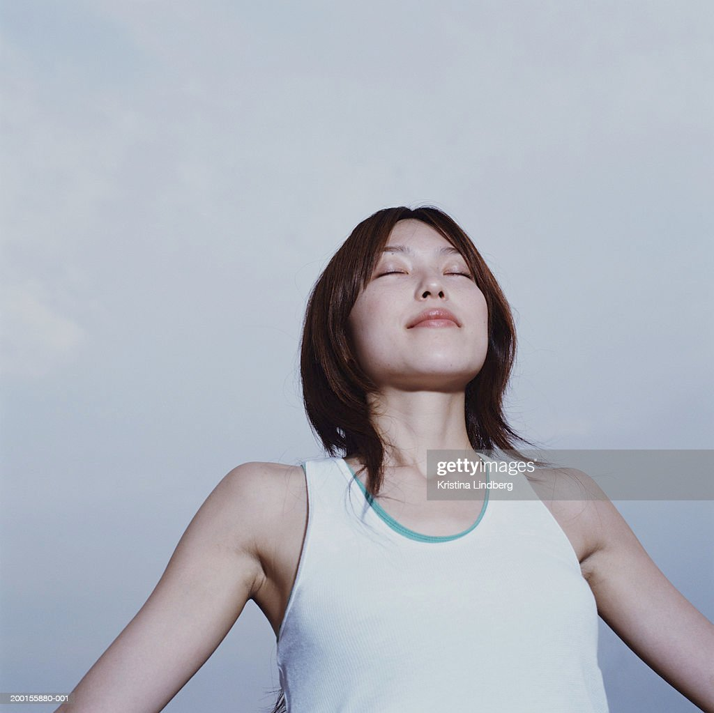 Young woman  with arms outstretched, eyes closed, low angle view : Stock Photo