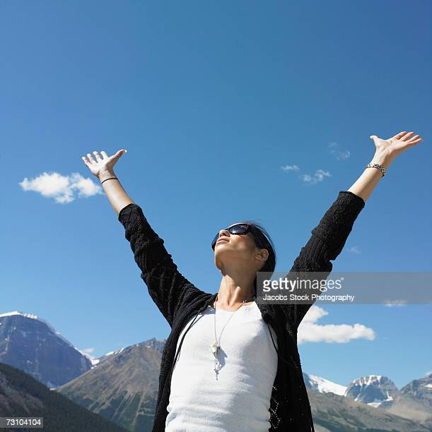 Young woman with arms outstretched, wearing sunglasses