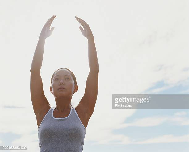 Young woman with arms up for yoga pose